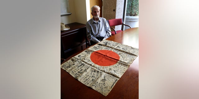 WWII veteran Marvin Strombo sits with the flag he will return to a fallen Japanese soldier's family.
