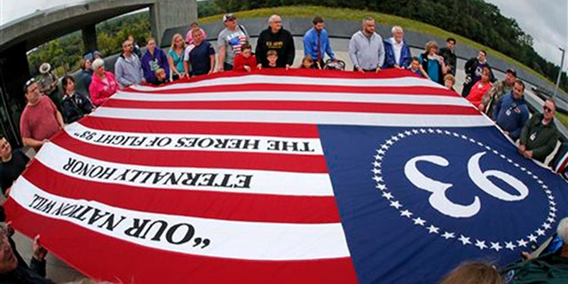 Visitors to the Flight 93 National Memorial in Shanksville, Pa., participate in a memorial service Thursday, Sept. 10, 2015, as the nation marks the 14th anniversary of the Sept. 11 attacks. (AP Photo/Gene J. Puskar)
