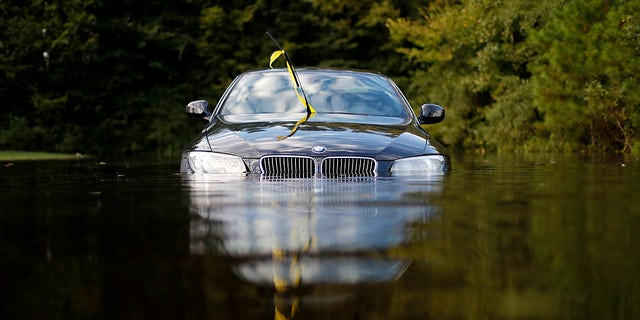 FILE- In this Tuesday, Sept. 18, 2018, file photo a car sits in a flooded parking lot at an apartment complex near the Cape Fear River as it continues to rise in the aftermath of Hurricane Florence in Fayetteville, N.C. As flooding continues in the Carolinas after Florence's massive rainfall, experts say high water will damage thousands of vehicles. (AP Photo/David Goldman, File)