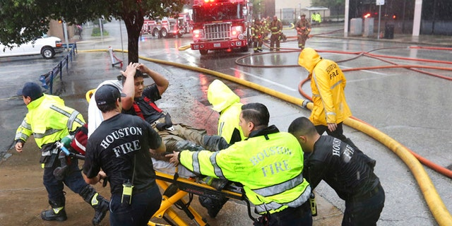 Rain from Tropical Storm Harvey falls as a firefighter is wheeled to a waiting ambulance after he became fatigued while fighting an office building fire in downtown in Houston, Texas, Monday, Aug. 28, 2017. (AP Photo/LM Otero)