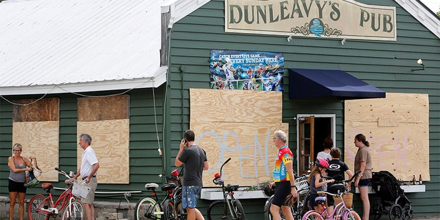 "Dunleavy's Pub on Sullivan's Island, South Carolina wrote ""open"" on their boarded up windows."