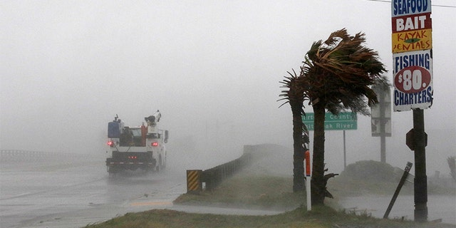 A work truck drives on Hwy 24 as the wind from Tropical Storm Florence blows palm trees in Swansboro North Carolina on Thursday.