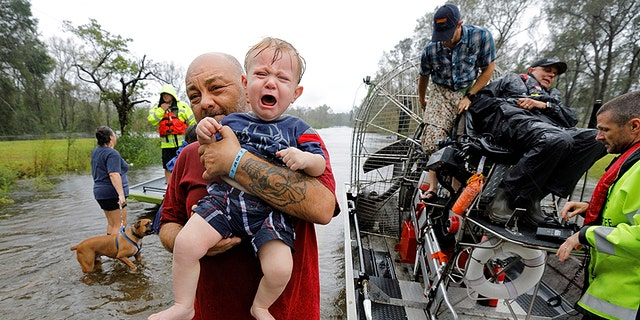 Oliver Kelly cries as he is carried off the sheriff's airboat during his rescue from rising flood waters in the aftermath of Hurricane Florence.