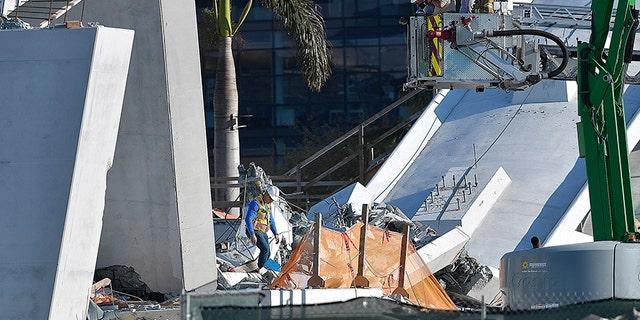 Miami-Dade Fire Rescue personnel inspect the scene following Thursday's bridge collapse.