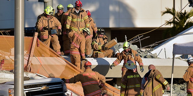 First responders inspect the damage after a pedestrian bridge collapsed near Florida International University in Miami.