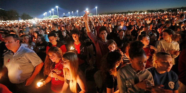 People hoist up their candles during a vigil for the victims of the Wednesday shooting at Marjory Stoneman Douglas High School.