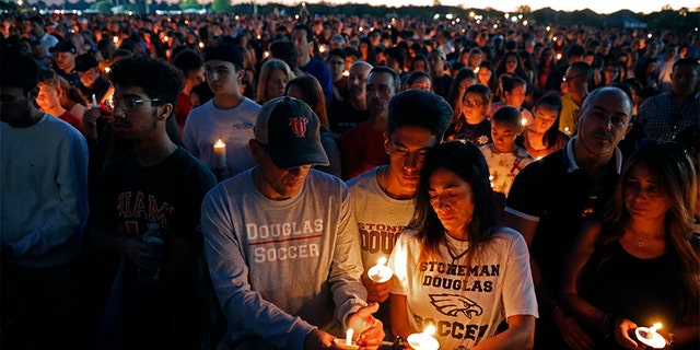 Jorge Zapata, Jr., center, a student at Marjory Stoneman Douglas High School, holds candles with his mother Lavinia Zapata, and father Jorge Zapata, Sr., during a candlelight vigil Wednesday.