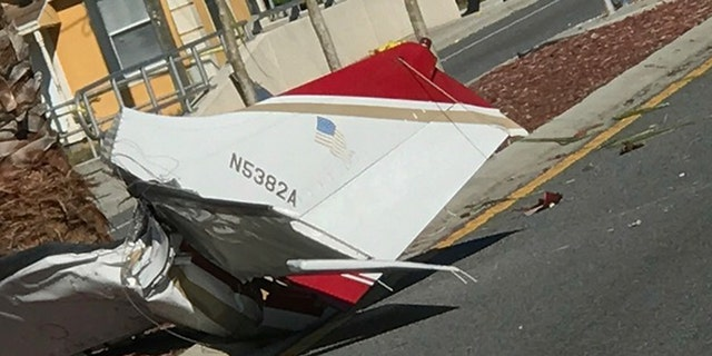 Pieces of a small plane lay on top of a road after small plane crashed in Kissimmee, Fla on Tuesday.
