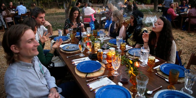 In this Oct. 2, 2016 photo, diners smoke marijuana as they eat dishes prepared by chefs during an evening of pairings of fine food and craft marijuana strains served to invited guests dining at Planet Bluegrass, an outdoor venue in Lyons, Colo.