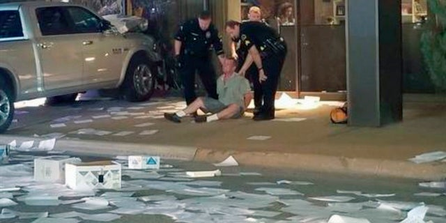 In this image taken from video by Fox 4, Michael Chadwick Fry is detained after crashing his pickup truck into the side of the Fox affiliate television station building in downtown Dallas.