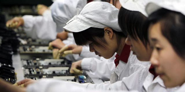 Workers at Foxconn are provided with masks at the start of each shift. In this Wednesday, May 26, 2010, file photography, staff members work on the production line at the Foxconn complex in Shenzhen, China.