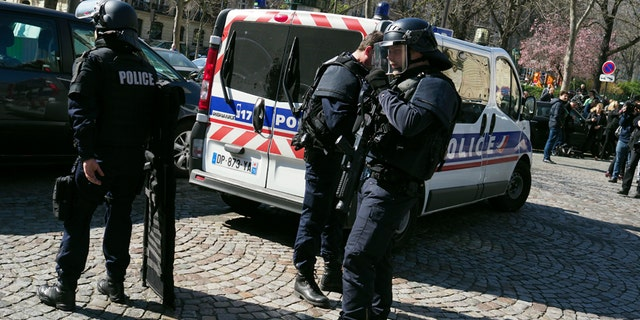 French police officers take position after letter bomb exploded at the French office of the International Monetary Fund, lightly injuring one person, Thursday March 16, 2017. A police official said no other damage was been reported in the incident. (AP Photo/Thibault Camus)