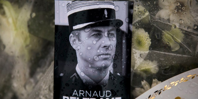 A photo of Lieutenant Colonel Arnaud Beltrame placed on a bunch of flowers at the main gate of the Police headquarters in Carcassonne, France, Saturday, March 24, 2018, following an attack on a supermarket in Trebes in the south of the country on Friday.