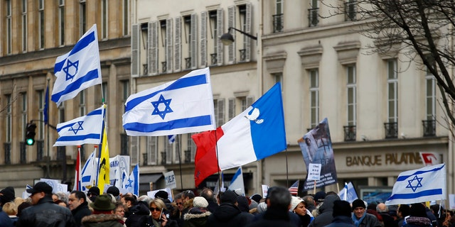 Pro-Israel demonstrators hold Isreali and France flags during a gathering in front of Israel embassy in Paris, France, Sunday, Jan. 15, 2017.