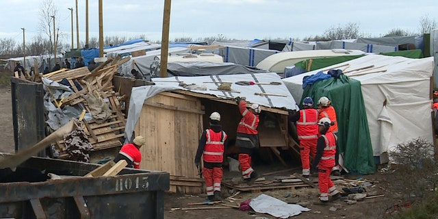 Feb. 29, 2016: Helmeted workers pull down makeshift structures where migrants sleep in the southern sector of the camp near the northern port of Calais, France.