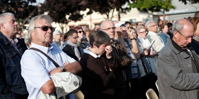 People attend a ceremony marking the first anniversary of the killing of French Catholic priest Jacques Hamel.