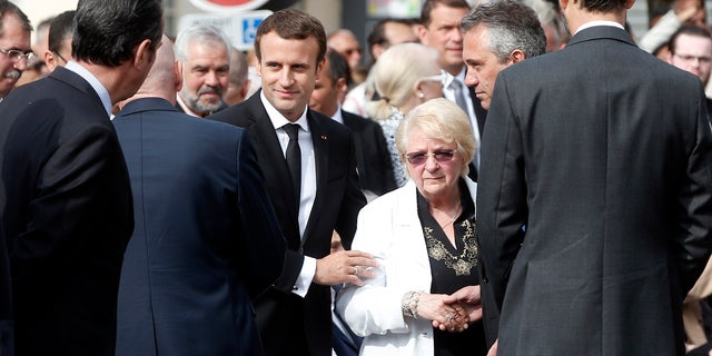 France's President Emmanuel Macron, center left, and sister of French Catholic priest Jacques Hamel, Roselyne, center right, attend a ceremony marking the first anniversary of the killing of French Catholic priest Jacques Hamel.