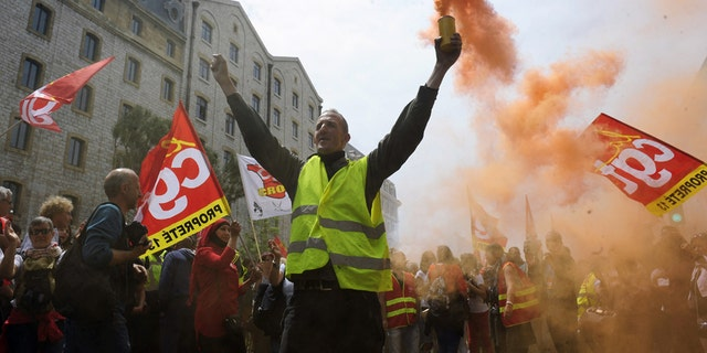 May 26, 2016: A demonstrator burns flares and shouts slogans during a demonstration in Marseille, southern France, on a day of nationwide strikes and protests over a labor reform.