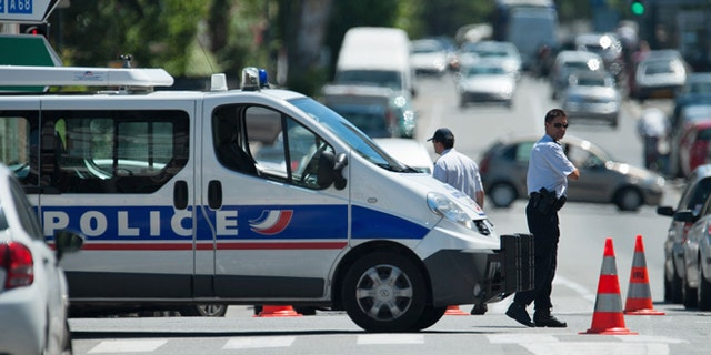 June 20, 2012: Police officers secure the area after a gunman took four people hostage in a bank in the southern French city of Toulouse and fired a shot, police said.