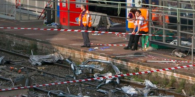 July 13, 2013: Railway's employees look at the scene where a train derailed at a station in Bretigny sur Orge, south of Paris.