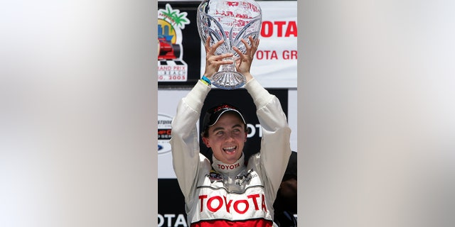 Actor Frankie Muniz sticks out his tongue as he hoists the trophy after winning the 29th Annual Pro/Celebrity Race in Long Beach, California, April 9, 2005.