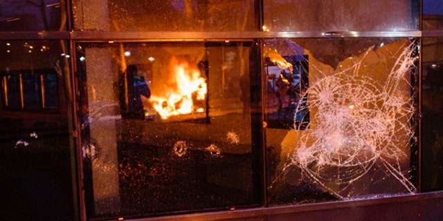 A fire set up by protestors is reflected in a broken window after a demonstration in Bobigny outside Paris, Saturday, Feb. 11, 2017. A peaceful demonstration protesting the alleged rape of a black youth by police has degenerated, with small groups setting at least one vehicle afire and throwing projectiles at police. (AP Photo/Aurelien Morissard)