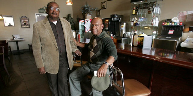 "FILE - In this March 5, 2009, file photo, the Rev. W. T.  ""Dub"" Massey, right, and Willie McLeod, left, pose at the counter where they were among the ""Friendship Nine"" who were jailed during 1960s civil rights ""sit-ins"" at what is now called the Old Town Bistro in Rock Hill, S.C.  A prosecutor on Wednesday, Jan. 28, 2015, is expected to ask a judge to vacate the arrests and convictions of the eight Friendship Junior College students and a civil rights organizer. (AP Photo/Mary Ann Chastain, File)"