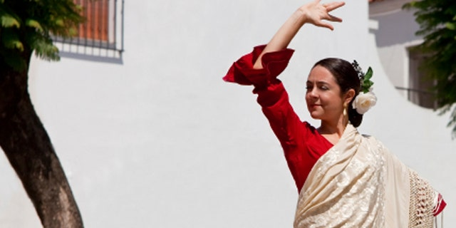 Woman traditional Spanish Flamenco dancer dancing in a red dress and cream shawl dancing in a town square with a stone fountain