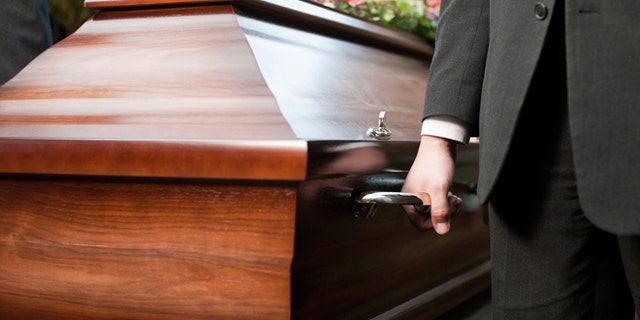 Religion, death and dolor  - coffin bearer carrying casket at funeral to cemetery