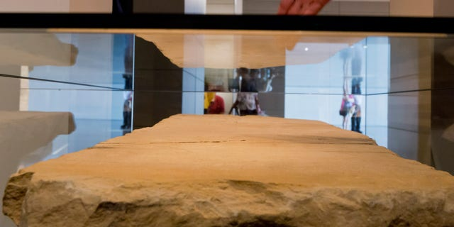 A visitor looking at the stone tablet called the Gabriel Revelation Stone on display at the Israel Museum. The stone is a centerpiece of an exhibition called, 'I am Gabriel,' which is written in Hebrew on the stone, with some 80 lines of writing. The tablet dates from the Second Temple era of the Jewish revolt after the death of Herod, and was discovered in 2007 near the Dead Sea scroll caves at the Dead Sea. The tablet is exhibited with a number of rare manuscripts that trace the figure of the Angel Gabriel across the early years of rabbinic Judaism, Christianity, and Islam. (EPA/JIM HOLLANDER)