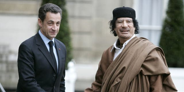 French President Nicolas Sarkozy, links, greets Libyan leader Col. Moammar Gadhafi upon his arrival at the Elysee Palace, in Paris, Des. 10, 2007.