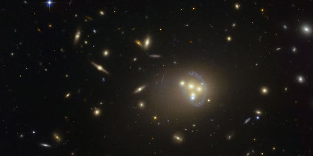 A Hubble Space Telescope image of galaxy cluster Abell 3827, where dark matter may have been observed interacting with itself during a galaxy collision.