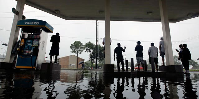 People watch heavy rain from the relative safety of a flooded gas station caused by Tropical Storm Harvey on Sunday, Aug. 27, 2017, in Houston.