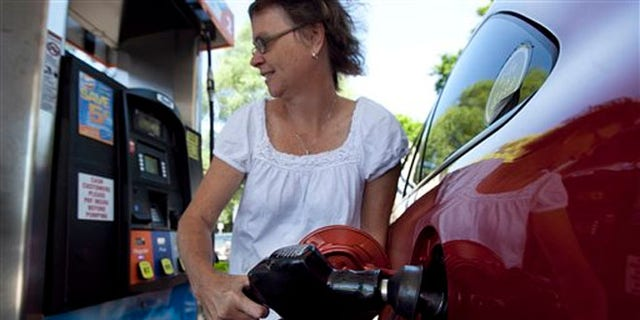 July 10, 2012: Suzanne Meredith, of Walpole, Mass., gases up her car at a Gulf station in Brookline, Mass. Gasoline is at $3.50 per gallon for the first time this summer after a sharp run-up in July.