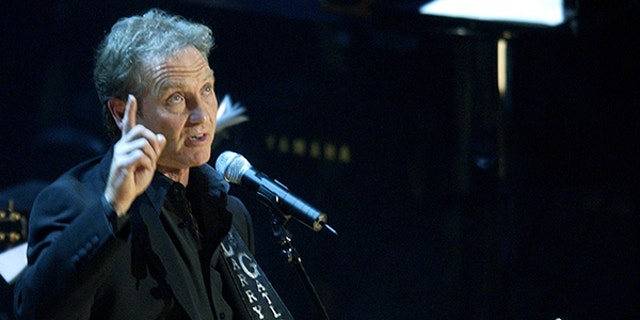 """Country music artist Larry Gatlin points to heaven after singing """"DiamondsIn The Rough,"""" during a tribute to the late country music legend JohnnyCash, at the Ryman Auditorium in Nashville, Tennessee, late November 10,2003. Cash died September 12, 2003, at the age of 71 from complications fromdiabetes. REUTERS/John Sommers II"""