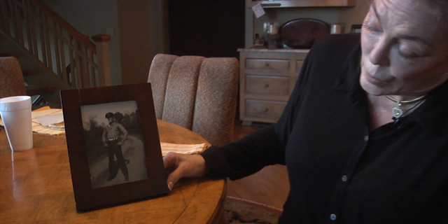 Pam Cunningham Averso displays a photo of her father in his Marine uniform.