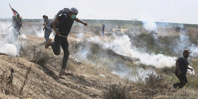 Palestinian protesters run for cover from teargas fired by Israeli troops during a protest at the Gaza Strip's border with Israel, Friday, April 6, 2018. (AP Photo/ Khalil Hamra)