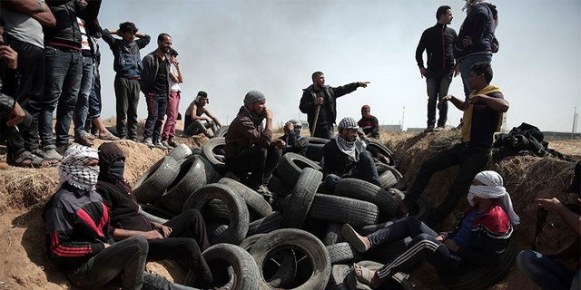 April 6, 2018: Palestinian protesters sit over tens of tires collected to be burned during a protest at the Gaza Strip's border with Israel.