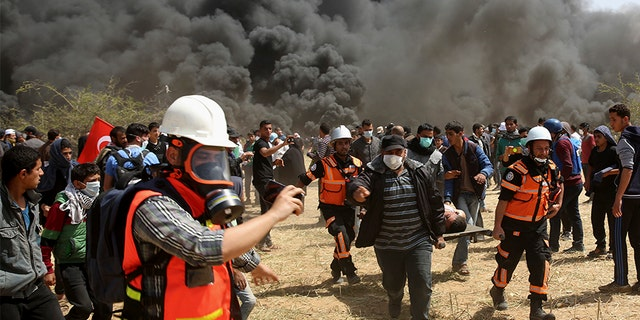 April 6, 2018: Palestinian protesters and civil defense evacuate a wounded youth during clashes with Israeli troops along Gaza's border with Israel.