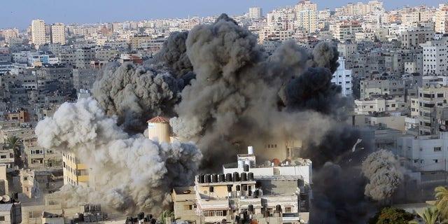 An Israeli airstrike hits the Said al-Mis'hal cultural center in Gaza City Thursday.