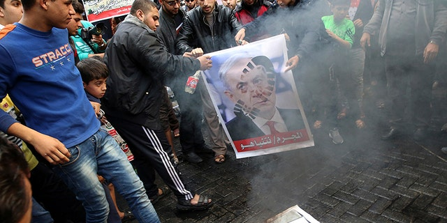 Hamas supporters burn a picture of Israeli Prime Minister Benjamin Netanyahu during a protest in the Gaza Strip.