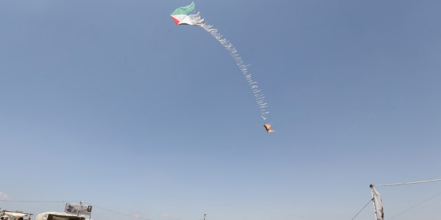 May 11, 2018: Palestinian demonstrators fly a flaming kite to be thrown at the Israeli side during a protest demanding the right to return to their homeland, at the Israel-Gaza border in the southern Gaza Strip.