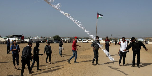 May 11, 2018: Palestinian demonstrators fly a flaming kite.