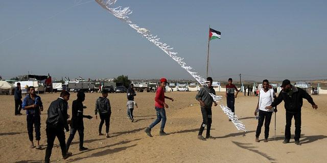 May 11, 2018: Palestinian demonstrators fly a flaming kite.