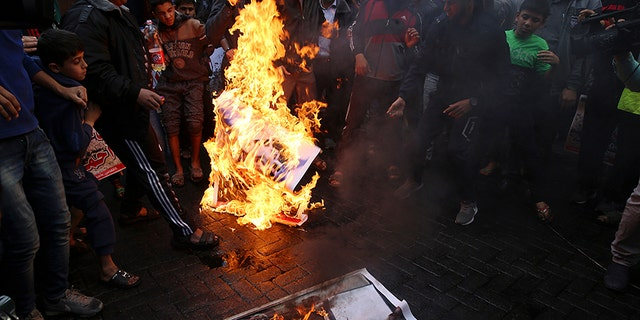 Hamas supporters burn a picture of Israeli Prime Minister Benjamin Netanyahu during protest against President Trump.