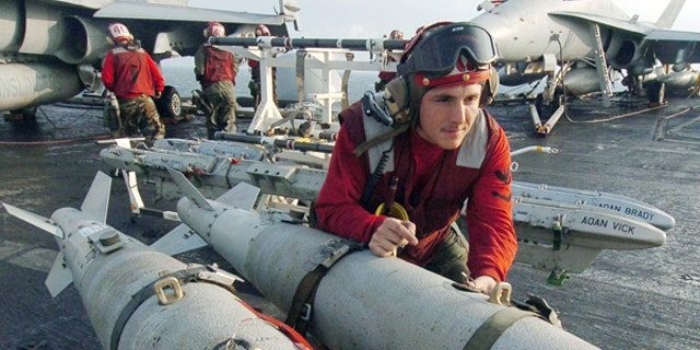 """U.S. Aviation Ordnanceman 3rd Class Joshua Silva, assigned to """"Gunslingers"""" of Strike Fighter Squadron One Zero Five (VFA-105), helps push a weapons skid loaded with three GBU-38 500 pound satellite guided bombs on the flight deck aboard USS Harry S. Truman ."""