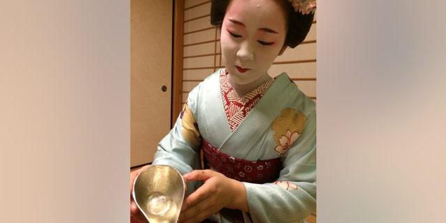 A maiko pouring sake.