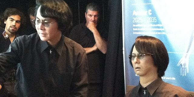 "Roboticist Hiroshi Ishiguro of Osaka University (left) demos his ""Geminoid"" android lookalike (right) at the Global Futures 2045 International Congress in New York."