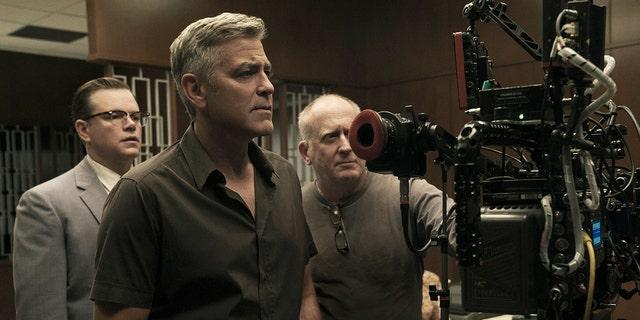 "Matt Damon, left, poses next to George Clooney, center, on the set of ""Suburbicon."""