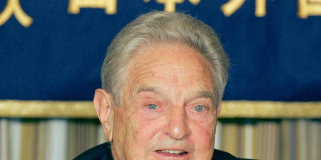 """Billionaire financier and philanthropist George Soros speaks to reporters at the Foreign Correspondents' Club of Japan in Tokyo Monday, Oct. 16, 2006. Soros said that China should allow its currency to appreciate in order to maintain economic stability. Shown at right on the table is a copy of the Japanese version of his latest book """"The Age of Fallibility."""" (AP Photo/Koji Sasahara)"""